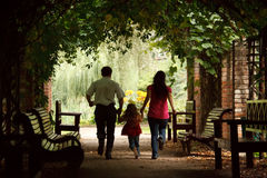 Parents with daughter escape on tunnel from ivy. Parents together with daughter escape on tunnel from ivy in summer garden Royalty Free Stock Images