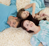 Parents and daughter on floor with heads together Royalty Free Stock Images