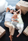 Parents and daughter on the floor with thumbs up Stock Photos