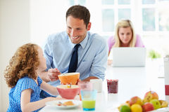 Parents And Daughter Having Breakfast In Kitchen Together Stock Photography