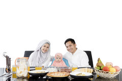 Parents and daughter having meal at dining table Stock Image