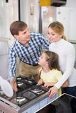 Parents with daughter in home appliance store royalty free stock image