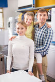 Parents with daughter in home appliance store royalty free stock images