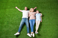 Parents and daughter lying together on green grass Stock Images