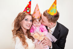Parents and daughter in party hats Royalty Free Stock Photos