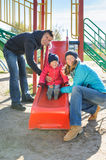 Parents with daughter playing at children`s slide. Joyful parents mother and father with excited little daughter having fun at sliding board outdoors at the Royalty Free Stock Photos