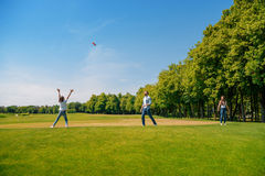 Parents with daughter playing with flying disk on green grass Royalty Free Stock Images
