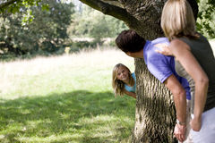 Parents and daughter playing hide and seek Royalty Free Stock Photos