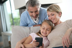 Parents with daughter playing on smartphone Royalty Free Stock Photography