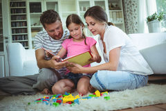 Parents and daughter reading a book while playing with building blocks Stock Images