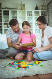 Parents and daughter reading a book while playing with building blocks Stock Photos