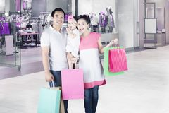 Parents and daughter with shopping bags Stock Images