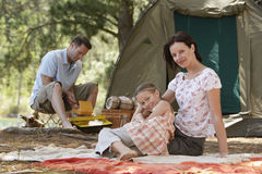 Parents With Daughter Sitting At Campsite Royalty Free Stock Image