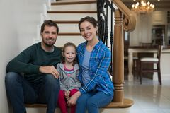 Parents and daughter sitting on stairs. At home Stock Photos