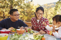 Parents with daughter sitting at table looking at each other Stock Photos