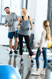 Parents and daughter with skipping ropes at health club. Young parents and daughter with skipping ropes at health club stock photo