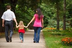 Parents with daughter walk on summer garden Stock Photos