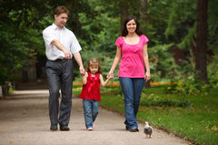 Parents with daughter walk on summer garden Royalty Free Stock Photography