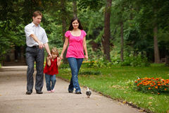 Parents with daughter walk on summer garden Stock Image