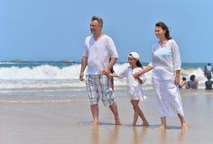 Parents with daughter walking on beach Royalty Free Stock Photos