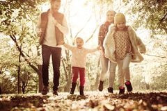 Happy family enjoying in autumn day. Parents with daughters in park stock photography