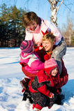Parents with daughters playing in snow Stock Image