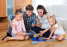 Parents and daughters with toy lotto. Cheerful parents and daughters with toy lotto at home Royalty Free Stock Image