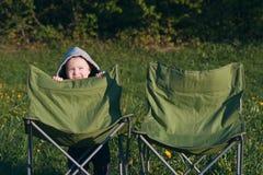 Parents de attente de petit garçon, une chaise pour la maman et papa contre le contexte des prés verts Le coucher de soleil images libres de droits