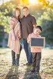 Parents de métis se tenant derrière le fils avec le panneau de craie vide Photographie stock