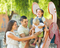 Parents de sourire aidant des enfants sur la glissière Photo libre de droits