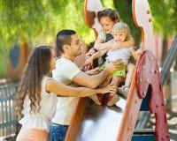 Parents de sourire aidant des enfants sur la glissière Images stock