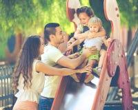 Parents de sourire aidant des enfants sur la glissière Images libres de droits