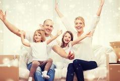 Parents de sourire et deux petites filles à la nouvelle maison Photos stock