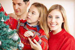 Parents decorating christmas tree. Together with her daughter Royalty Free Stock Images
