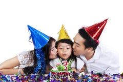Parents embrassant leur enfant en fête d'anniversaire Image stock