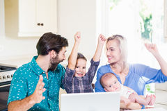 Parents enthousiastes et enfants à l'aide de l'ordinateur portable dans la cuisine Photos stock