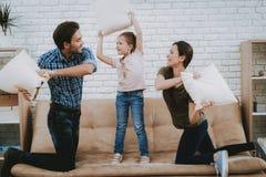 Parents et combat d'enfant avec des oreillers sur le sofa de Brown images libres de droits