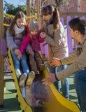 Parents et deux filles au terrain de jeu Photos libres de droits