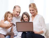 Parents et deux filles avec l'ordinateur portable et la carte de crédit Photographie stock libre de droits