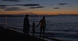 Parents et enfant marchant par la mer dans le crépuscule banque de vidéos