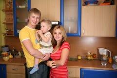 Parents et enfant sur des mains dans la cuisine 2 Photos stock