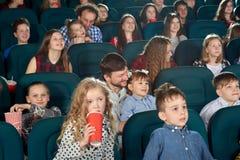 Parents et enfants observant le film dans le cinéma et l'amusant photo libre de droits
