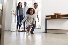 Parents et enfants renvoyant l'ouverture à la maison Front Door And Running Inside photo libre de droits