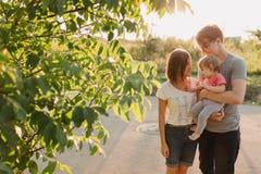 Parents et fille de bébé dehors dans le coucher du soleil Photos stock