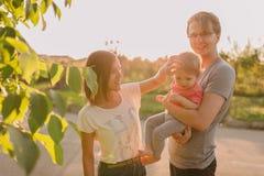 Parents et fille de bébé dehors dans le coucher du soleil Image stock