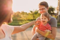Parents et fille de bébé dehors dans le coucher du soleil Photographie stock libre de droits