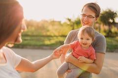 Parents et fille de bébé dehors dans le coucher du soleil Photographie stock
