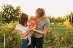 Parents et fille de bébé dehors dans le coucher du soleil Images stock
