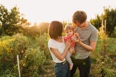 Parents et fille de bébé dehors dans le coucher du soleil Image libre de droits