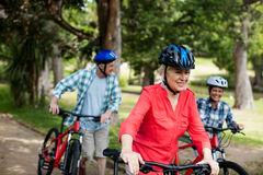 Parents et fille marchant avec la bicyclette en parc Photographie stock libre de droits